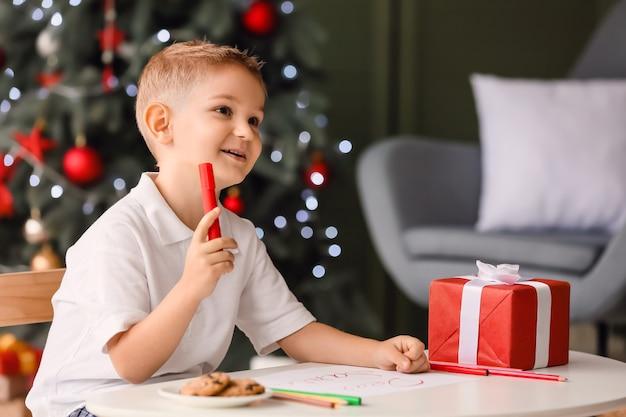 Schattige kleine jongen die op kerstavond thuis een brief schrijft aan de kerstman