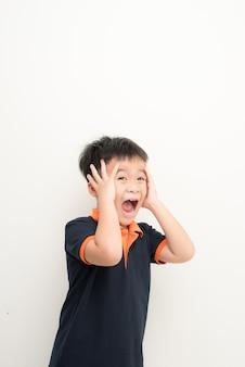 Schattige kleine jongen die oren bedekt met handen, op witte achtergrond