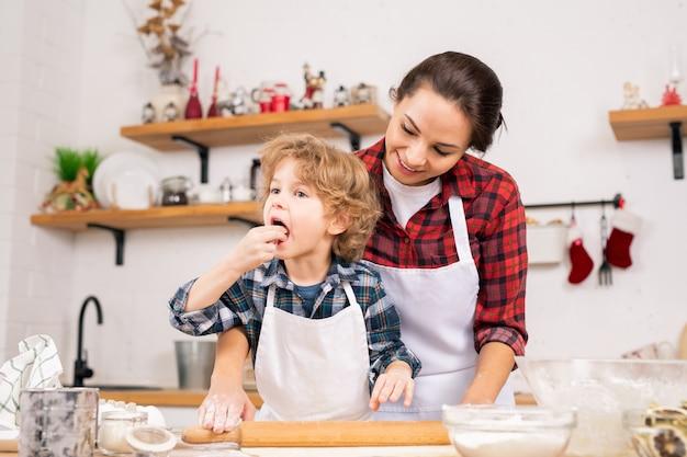 Schattige kleine jongen die zelfgemaakt deeg proeft terwijl hij moeder helpt om het op tafel te rollen voordat hij gebak of koekjes maakt