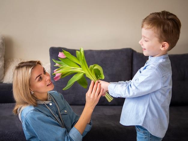 Schattige kleine jongen die zijn moeder met bloemen verrast