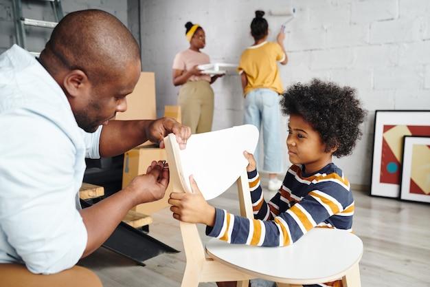 Schattige kleine jongen die zijn vader helpt met het monteren van een houten stoel tegen moeder en zus die de muur van de woonkamer in witte kleur schilderen