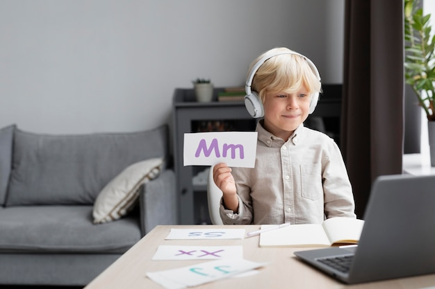 Schattige kleine jongen doet een online sessie logopedie