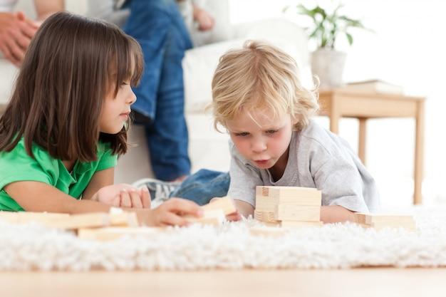 Schattige kleine jongen domino spelen met zijn zus op de vloer