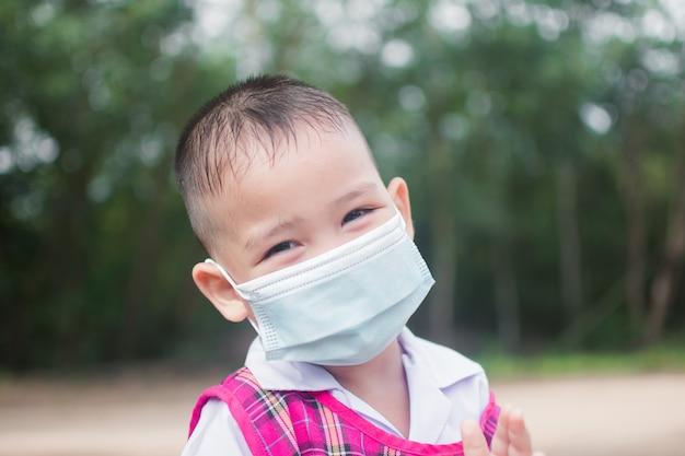 Schattige kleine jongen draagt masker ter bescherming van coronavirus of covid 19.