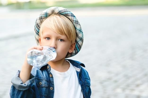 Schattige kleine jongen drinkwater uit de plastic fles. kind drinkt water buiten.