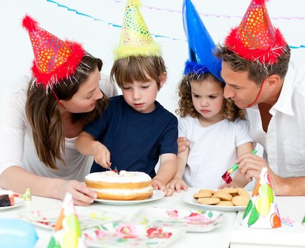 Schattige kleine jongen een verjaardagstaart snijden voor zijn gezin
