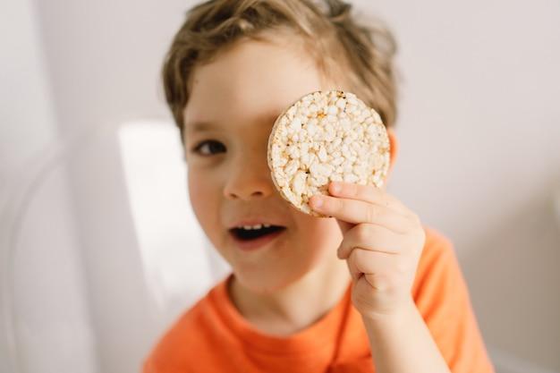 Schattige kleine jongen eet knäckebröd gezonde levensstijl en voedingsconcept