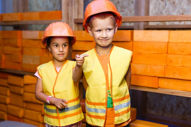 Schattige kleine jongen en meisje spelen met speelgoed gereedschap en lacht naar de camera