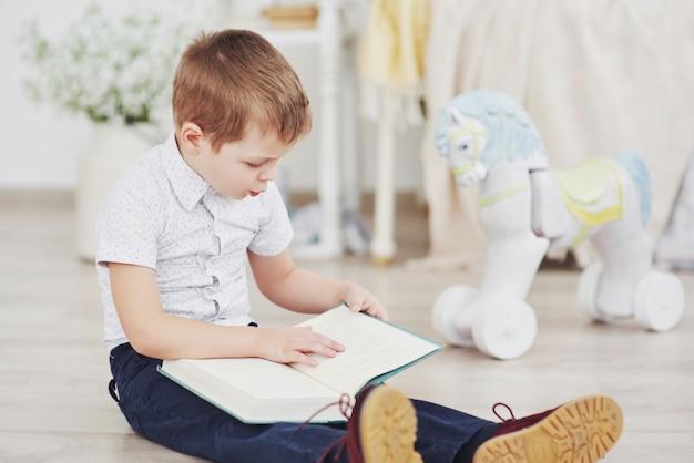 Schattige kleine jongen gaat voor het eerst naar school. kind met tas en boek. kid maakt een aktetas, kinderkamer op een achtergrond