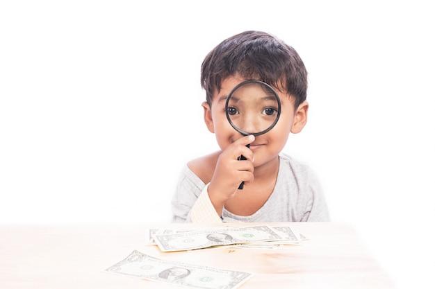 Schattige kleine jongen gebruik vergrootglas op zoek naar geld