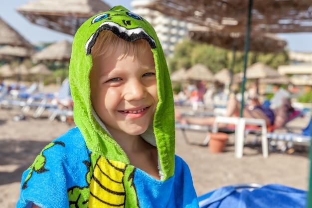 Schattige kleine jongen grappige handdoek dragen op het strand