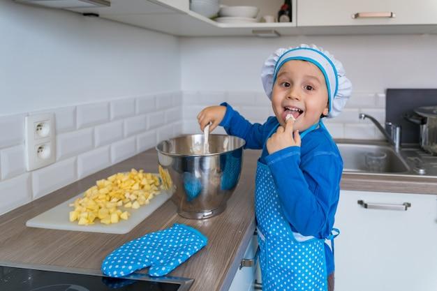 Schattige kleine jongen helpen en appeltaart bakken in de keuken van het huis, binnen