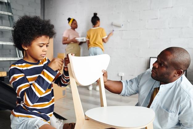 Schattige kleine jongen helpt zijn vader met het monteren van een stoel terwijl hij zijn rug vastmaakt tegen moeder en zus die de muur van de woonkamer in witte kleur schilderen