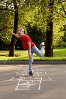 Schattige kleine jongen hinkelspel buiten. straat kinderspelen. selectieve aandacht.