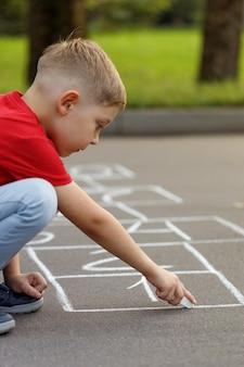 Schattige kleine jongen hinkelspel met wit krijt tekenen op speelplaats. activiteitenspel voor kinderen op speelplaats buiten.