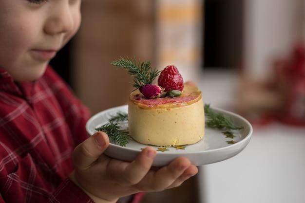 Schattige kleine jongen houden en mini cheesecake eten met een kerstster. desserts voor kinderen. hij geniet ervan.
