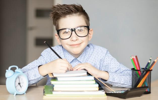 Schattige kleine jongen huiswerk. kind leren vijand school.