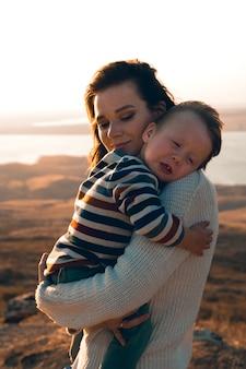 Schattige kleine jongen in de armen van zijn moeder. vrouw die thuis haar pasgeboren zoon draagt.