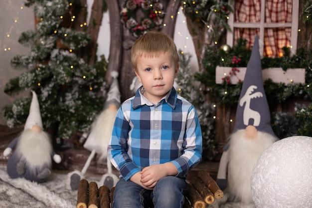 Schattige kleine jongen in de buurt van kerstboom en kabouters.