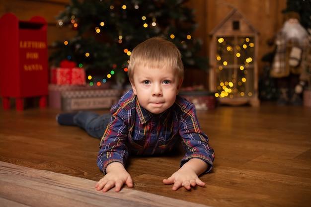 Schattige kleine jongen in de buurt van thuis boom versierd voor kerstmis.