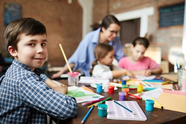 Schattige kleine jongen in de kunst klasse