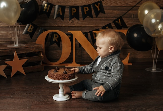 Schattige kleine jongen in een grijs pak viert zijn eerste verjaardag en breekt een taart op een bruine achtergrond met decor