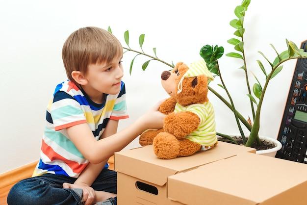Schattige kleine jongen in een nieuw huis. huisvesting van een jong gezin met een kind. familie verhuist naar een nieuw appartement. jongen speelt in hun nieuwe appartement. schattige jongen helpt dozen uitpakken.