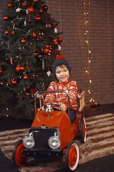 Schattige kleine jongen in een rode trui. kind bij de kerstboom.