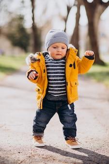 Schattige kleine jongen in gele jas die eerste babystapjes doet
