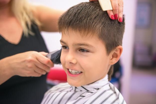 Schattige kleine jongen in gestripte salon cape in kapperszaak.