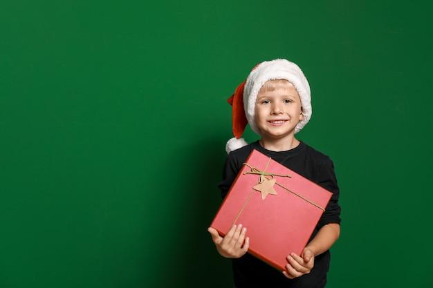 Schattige kleine jongen in kerstman hoed en met kerstcadeau