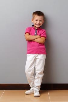 Schattige kleine jongen in roze t-shirt poseren