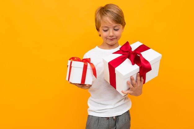 Schattige kleine jongen in t-shirt en broek houdt een doos met cadeau zelf geïsoleerd op gele achtergrond