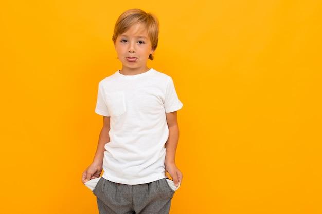 Schattige kleine jongen in t-shirt en broek houdt zijn handen in zakken geïsoleerd op geel