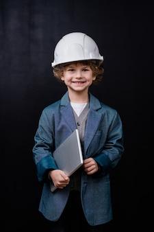 Schattige kleine jongen in veiligheidshelm en formalwear die gevouwen laptop houdt terwijl hij naar je kijkt met een glimlach geïsoleerd tegen zwarte ruimte