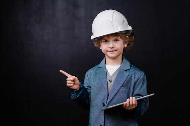 Schattige kleine jongen in veiligheidshelm en formalwear digitale tablet vasthouden terwijl hij naar je kijkt en opzij wijst tegen zwarte ruimte
