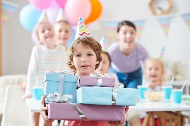 Schattige kleine jongen in verjaardag glb bedrijf stapel verjaardagscadeautjes thuis partij met vrienden