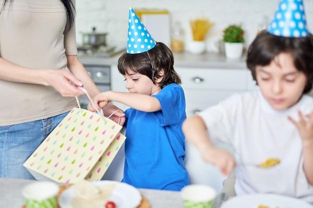 Schattige kleine jongen in verjaardagspet die cadeautjes van zijn ouders ontvangt. latijnse familie die verjaardag samen thuis viert. jeugd, viering concept. selectieve focus