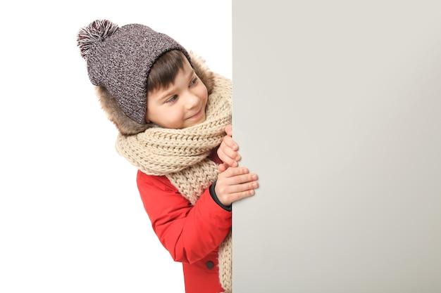 Schattige kleine jongen in warme kleren met bord