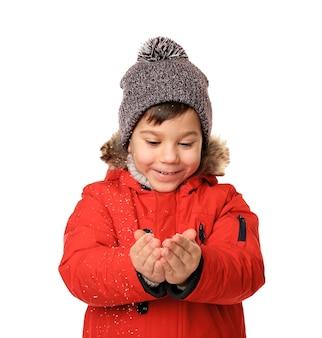 Schattige kleine jongen in warme kleren spelen met sneeuw op witte muur