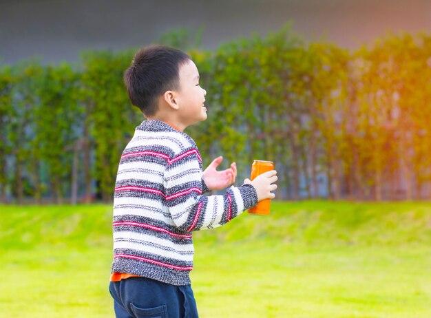 Schattige kleine jongen is lopen en tablet houden in handen in het park
