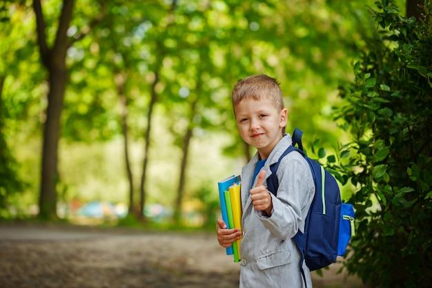 Schattige kleine jongen jongen met boeken en rugzak, toont klasse op groene natuur achtergrond. terug naar school-concept.