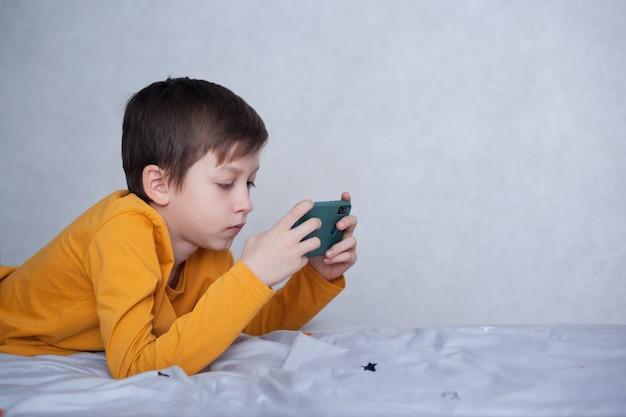 Schattige kleine jongen jongen speelt in videogame op zijn smartphone