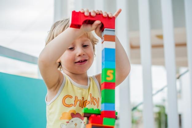 Schattige kleine jongen jongen spelen met veel kleurrijke plastic blokken binnen. actief kind dat pret heeft met het bouwen en creëren van toren. bevordering van vaardigheden en creativiteit
