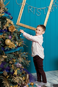 Schattige kleine jongen kerstboom versieren. jong kind in lichte slaapkamer met winterdecoratie. gelukkige familie thuis. kerstmis nieuwjaar december tijd voor viering concept