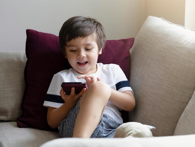 Schattige kleine jongen kijken cartoons op mobiele telefoon