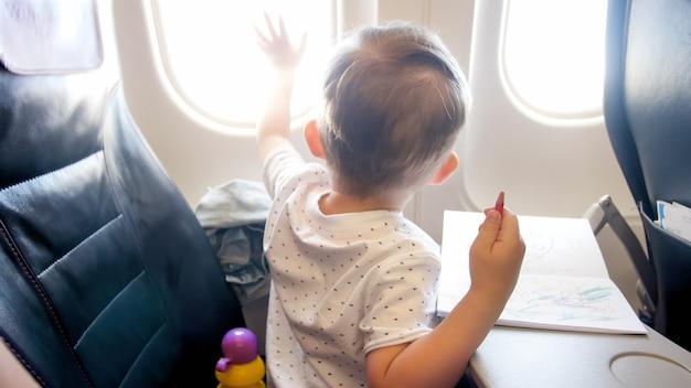 Schattige kleine jongen kijkt uit het raam in het vliegtuig tijdens de vlucht.