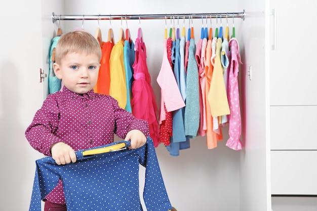 Schattige kleine jongen kleren in garderobe kiezen
