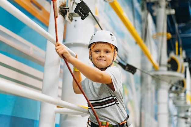 Schattige kleine jongen klimmen in avonturenpark langs hindernisbaan. hoogtouwpark binnen