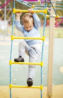 Schattige kleine jongen klimmen op een jungle gym